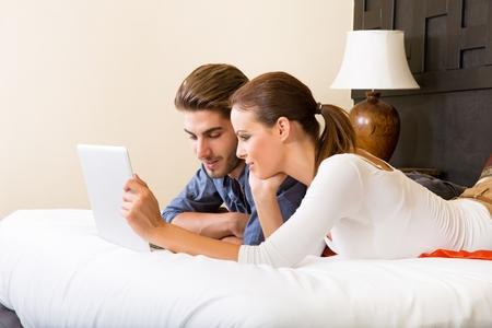 pareja en la cama: Pareja joven con un ordenador port�til en una habitaci�n de hotel asi�tico