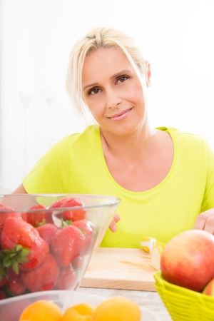 woman eating fruit: Mature woman preparing a smoothie