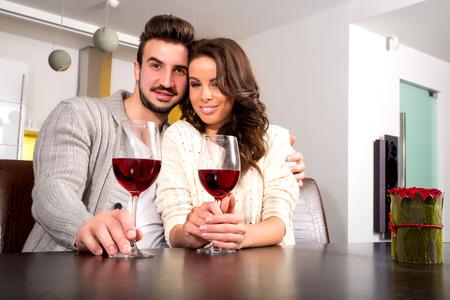 diner romantique: Un jeune couple en dégustant un verre de vin au moment de la nuit à la maison.