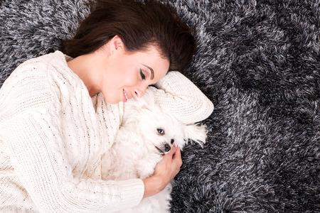 amigos abrazandose: Una joven y bella mujer abrazando a su perro en la alfombra de la sala de estar. Foto de archivo