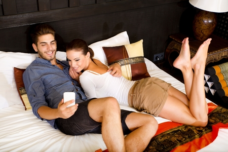 honeymoon suite: Young couple using a Tablet PC in a asian hotel room