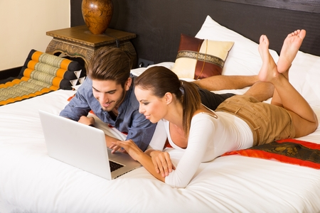 Young couple using a laptop in a asian hotel room photo