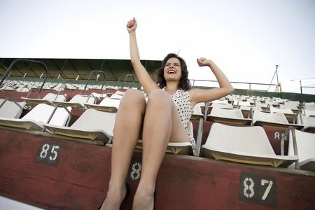 Retro girl sitting in stadium Stock Photo