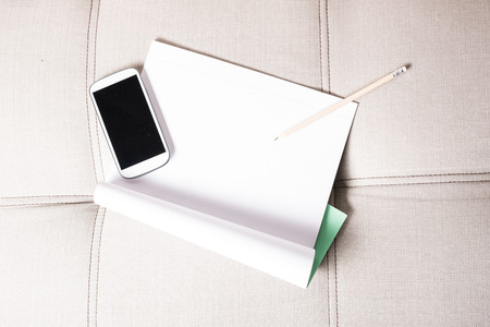 exercise book: A smartphone and a exercise book lying on the sofa