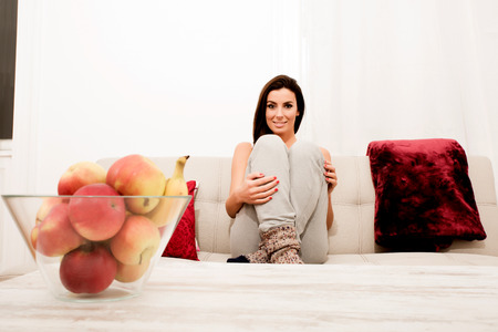 wornout: Young beautiful woman sitting on the couch wearing wornout socks Stock Photo