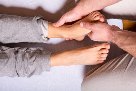 adult foot: A young adult woman receiving a foot massage by a male masseur.
