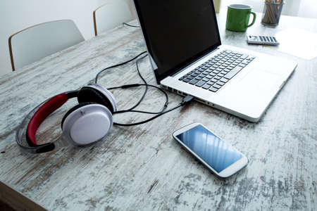 audifonos: Electrónica y un ordenador portátil en un escritorio Foto de archivo