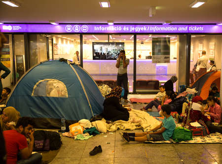 information point: BUDAPEST, HUNGARY - SEPTEMBER 04: Refugees camp in front of the information point in underground section of the Train Station Keleti Palyudvar on September 04, 2015 in Budapest, Hungary.