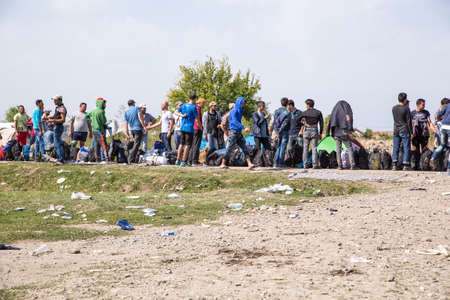 waiting in line: TOVARNIK, CROATIA - SEPTEMBER 19: Stranded Refugees form a waiting line with luggage after their arrival from Serbia on September 19, 2015 in Tovarnik, Croatia.