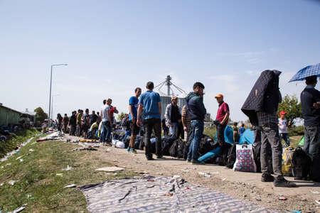 file d attente: Tov�rn�k, Croatie - 19 SEPTEMBRE: Stranded r�fugi�s forment une file d'attente avec des bagages apr�s leur arriv�e de la Serbie le 19 Septembre, 2015 Tovarnik, Croatie.