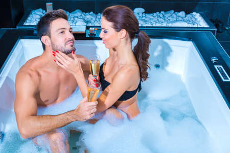 whirlpool: Beautiful young couple relaxing together and drinking Champagne in the Whirlpool.