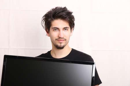 flatscreen: A young hispanic man holding a flatscreen TV. Stock Photo