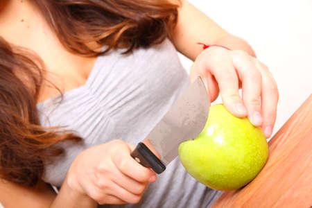 annals: A young adult woman cutting fruits in the kitchen. Stock Photo