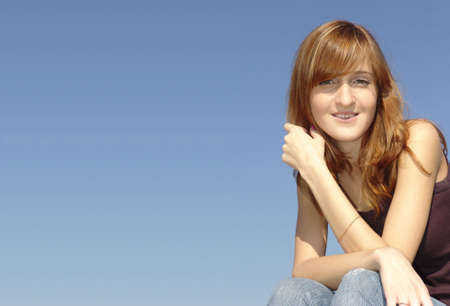 Young and pretty girl sitting against daylight sky background - trere are a lot of space for adding your text photo