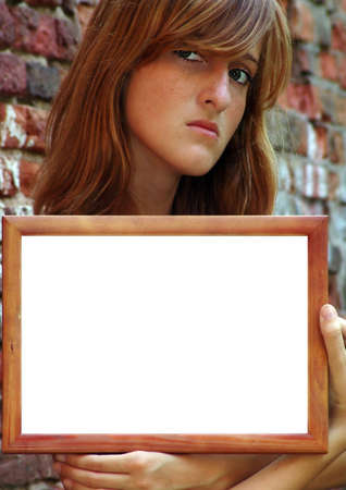 Young pretty girl with wooden frame. Specially for your text or pictures. photo
