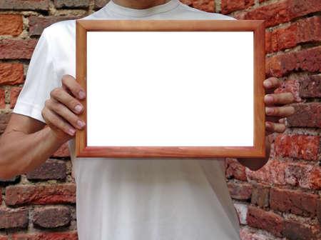 Man i white t-shirt shows your text or picture in wooden frame photo
