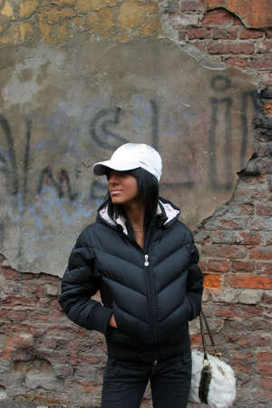 Young pretty fashion girl standing alone near cracked wall. Wearing snowy white cap Stock Photo - 813652