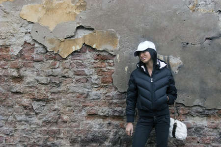 Casual girl with white cap and bag posing in the street near grungy wall Stock Photo - 813651