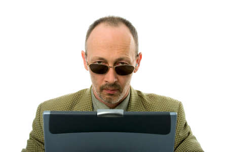 Serious  businessman with laptop looking over glasses. Isolated over white. photo