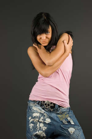 Young and fashionable brunette  posing in pink t-shirt and blue jeans photo