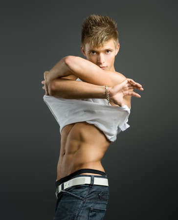 Handsome  guy with athletic body  in white t-shirt and jeans posing in studio