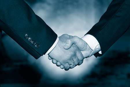 merger: Business handshake over abstract blue background