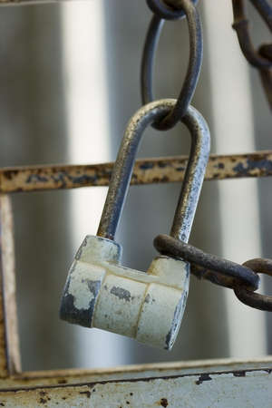 Old vintage padlock fixed on grungy metal fence photo