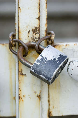 keep gate closed: Old vintage padlock fixed on grungy metal fence