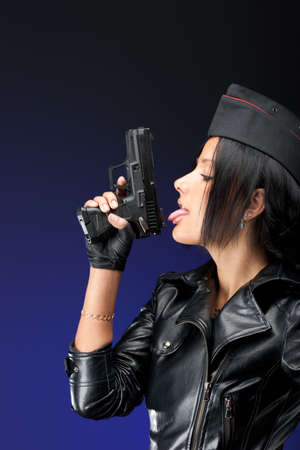 Beautiful woman licking black handgun photo