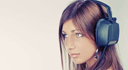 Beautiful young woman listening music and looking afar photo