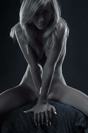 Naked blonde woman posing over dark background Stock Photo