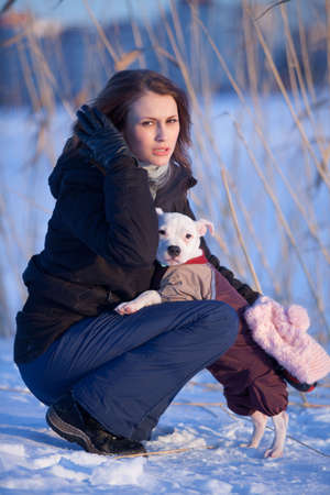 Girl with her white little dog. walking outdoors in winter photo