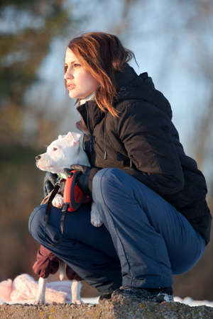 Girl with her white little dog. walking outdoors in winter