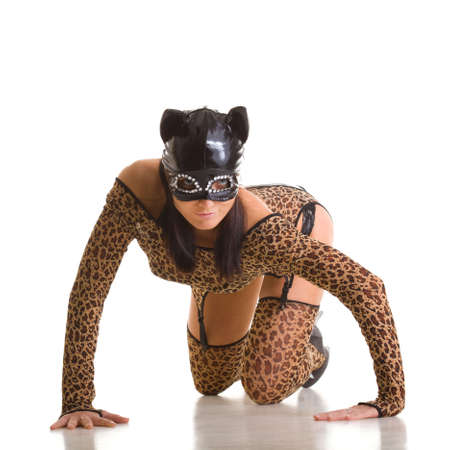 Young sexy woman in cat costume and mask posing on the studio floor. photo
