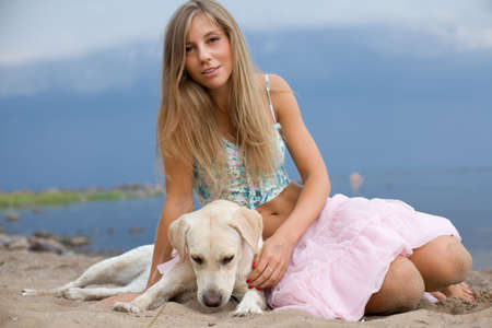 Young woman with her dog at the beach photo