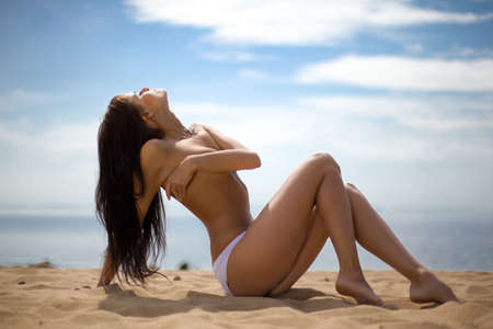 Topless brunette woman relaxing on the beach Stock Photo