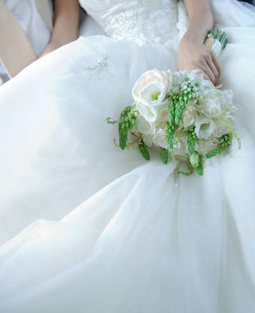 Beautiful white bridal bouquet with large space for your text on wedding dress Stock Photo