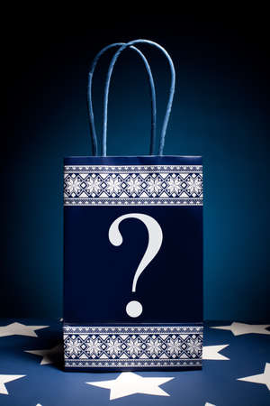 Gift bag with question symbol on it. Concept - thinking about holiday gifts.  photo