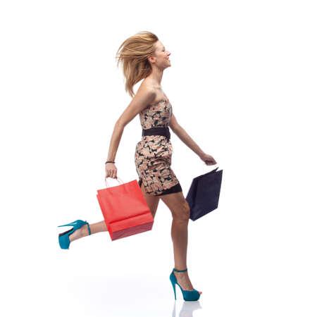piernas con tacones: Ejecutando mujer con bolsas de compra. Ligero desenfoque de movimiento   Foto de archivo