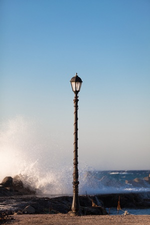 Lonely lamppost standing near the stormy sea. Oia, Santorini island, Greece photo