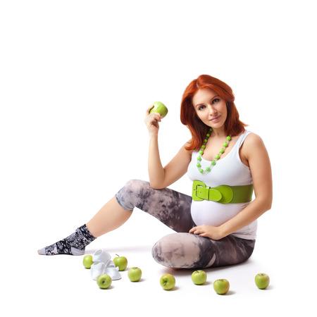 Beautiful pregnant woman holding green apple photo