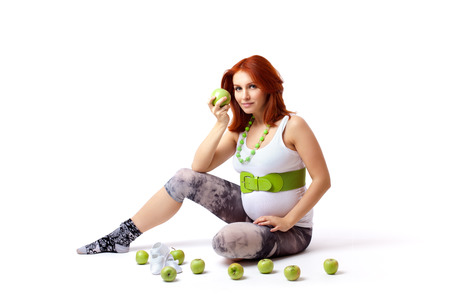Beautiful pregnant woman holding green apple photo