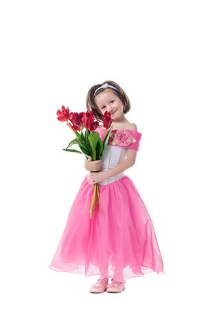 Happy little girl with red tulips. Isolated on white background photo