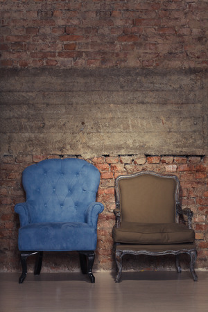 Two antique chairs against a grungy brick wall photo