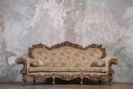 muebles antiguos: Sofá antiguo contra el fondo de estuco de edad Foto de archivo