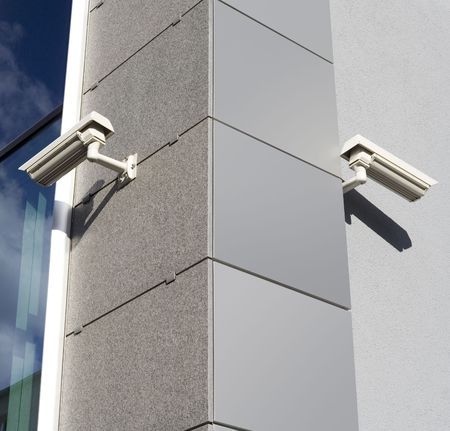 Security cams attached on corner of the building photo