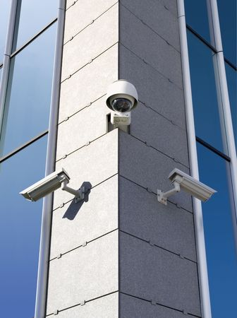 Three security cameras attached on building corner photo