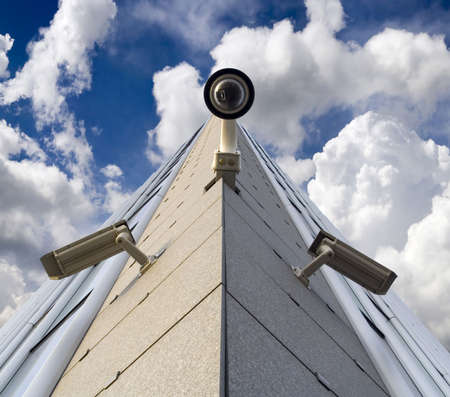 Three security cameras opposite the sky
