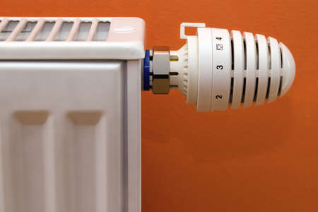warmness: Radiator heater with thermostat isolated on orange background Stock Photo