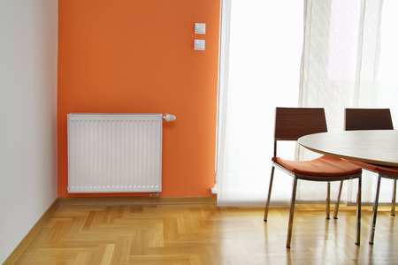 Heating Readiator on the Orange Wall Stock Photo - 22980448